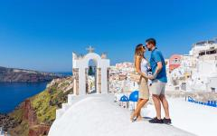 young couple stand on white church roof top with the sea in the background