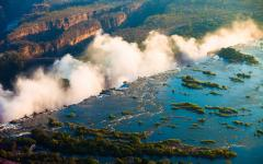 The edge of Victoria Falls with the waterfall's mist rising into view | Zambia, Africa