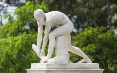 marble statue of a naked man bending down