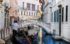 A gondola carries tourists along the Venice canals, Italy.