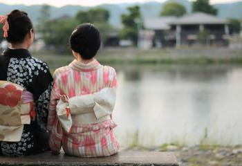 Women look over a river in traditional Japanese dress.