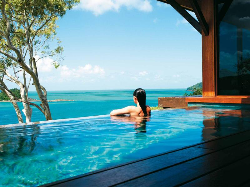 Woman Soaks In Plunge Pool Looking Out To The Ocean
