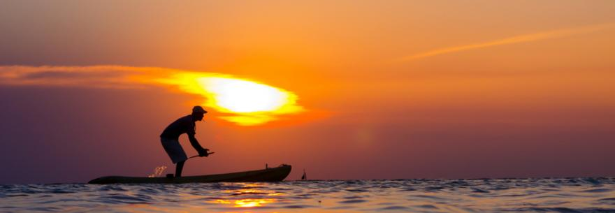 A paddleboarder in Caye Caulker at sunset.