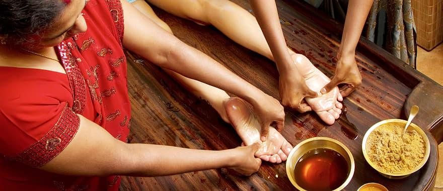 Women getting foot massage with oil in India.