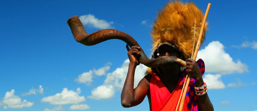Kenya Masai warrior blowing into a long twisted horn | Maasai Mara National Park