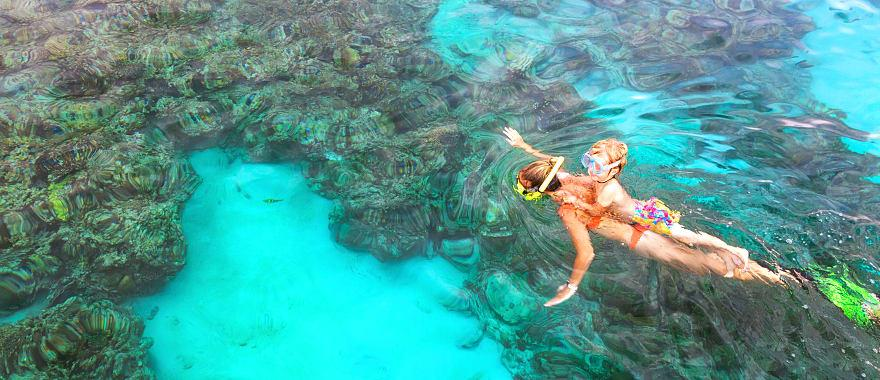 Indonesia Bali mother, kid in snorkeling mask dive underwater, explore tropical fishes in coral reef sea pool.