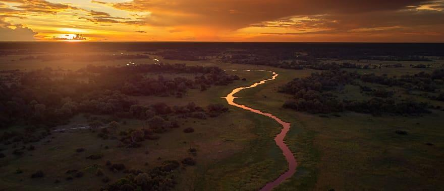 The sun sets over the Moremi forest, with the river Khwai running thru the Okavango Delta in Botswana