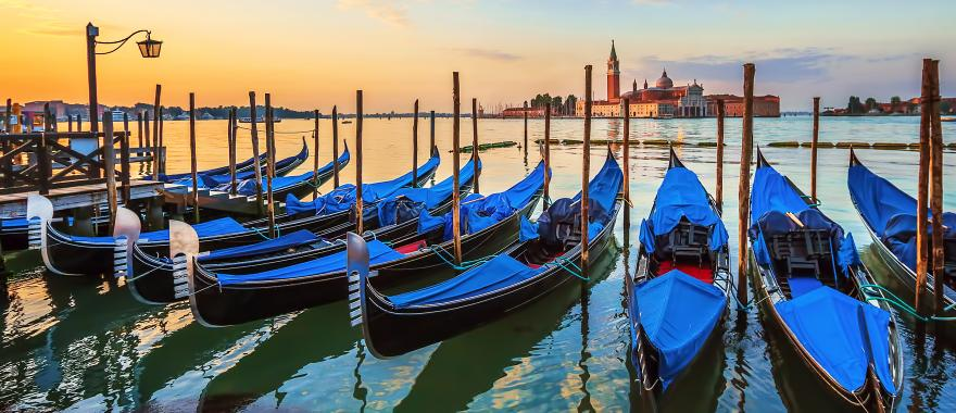 Row of traditional blue-colored gondolas parked on the Grand Canal | Venice, Italy
