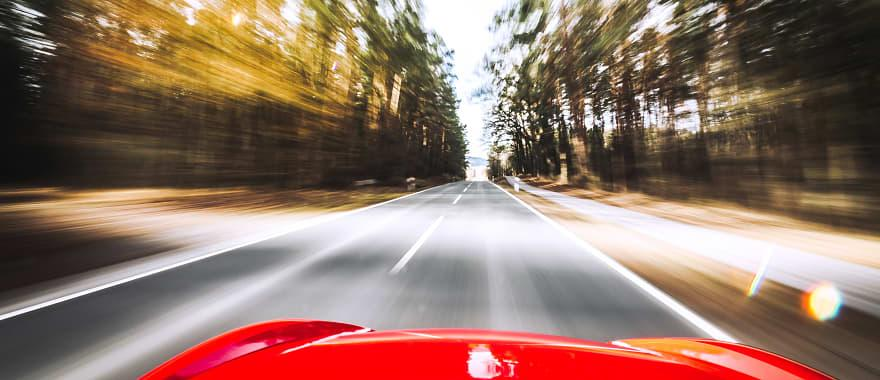 hood of red sports car driving through countryside.
