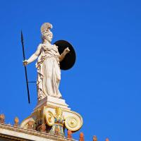 White marble statue of the Greek goddess Athena with a clear blue sky in the background