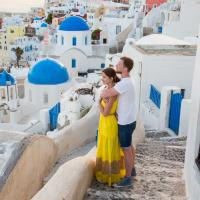 a couple look at the view amongst white and colorful buildings at sunset