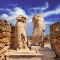 statues of cleopatra and dioscorides amongst archaeological ruins in greece